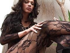 Gorgeous brunette shemale in body stocking strokes her cannon