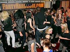 A large group of people, most of them girls, is dancing in a disco....