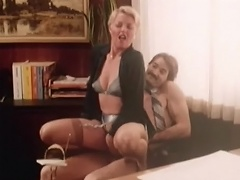 A guy is sitting naked in an office chair with a blonde woman on his...